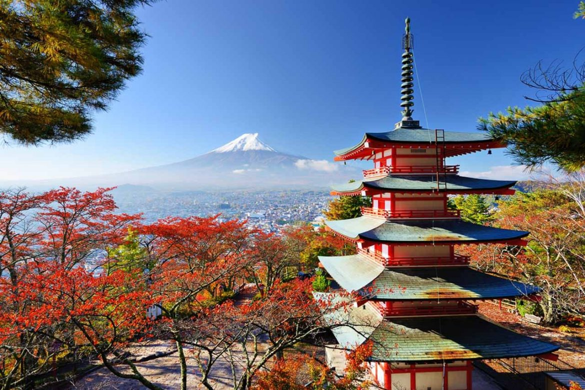 Red and green pagoda surrounded by red foliage, and overlooking snowcapped Mount Fuji in the distance