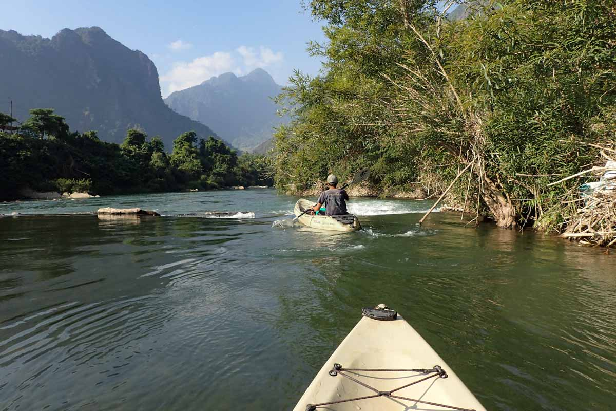Two people kayaking down a river surrounded by limestone mountains