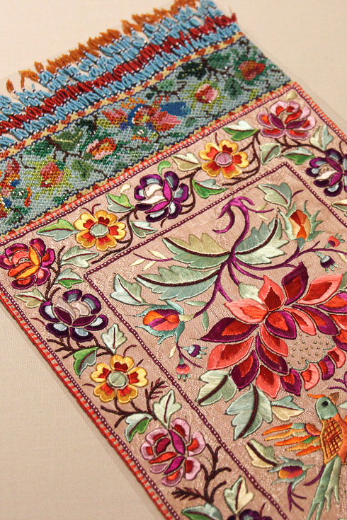An intricately embroidered table runner with beaded fringing
