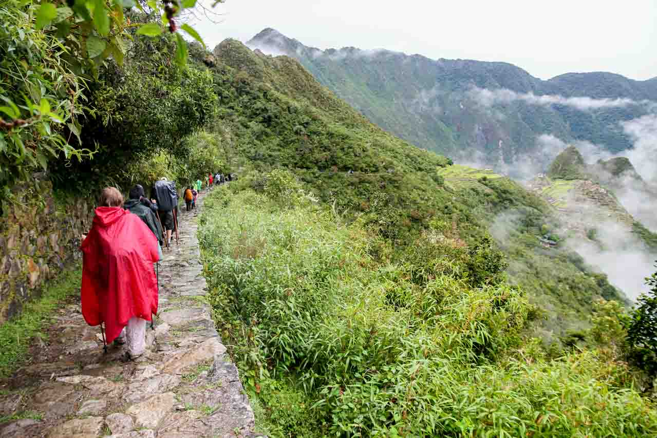 Hikers on the last stretch of Inca Trail with Machu Picchu off to the distance.