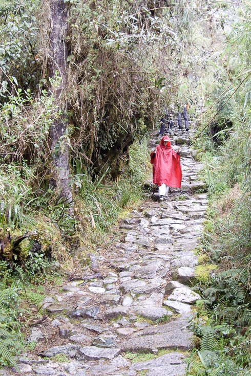 Woman in red poncho carefully descending a wet, stone path