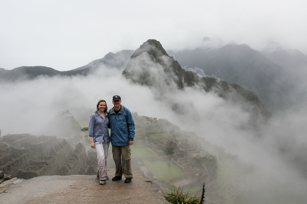 Couple standing infront of misty mountain scenery and archaeological site