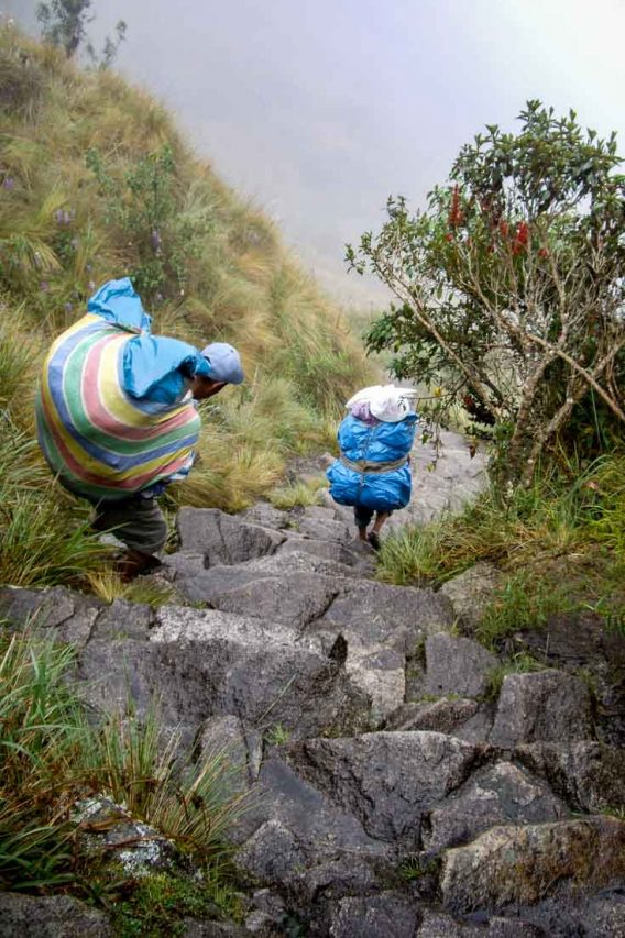 Our porters descend steep stone stairs wearing rubber sandals and carrying enormous packs.