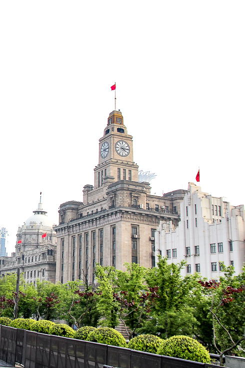 Image of colonial buildings with clocktower and Chinese flags, viewed over garden