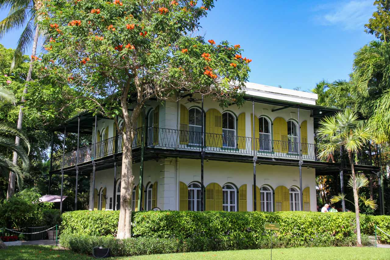 Exterior front view of Hemingway's home in Key West with citrine shutters and arched windows