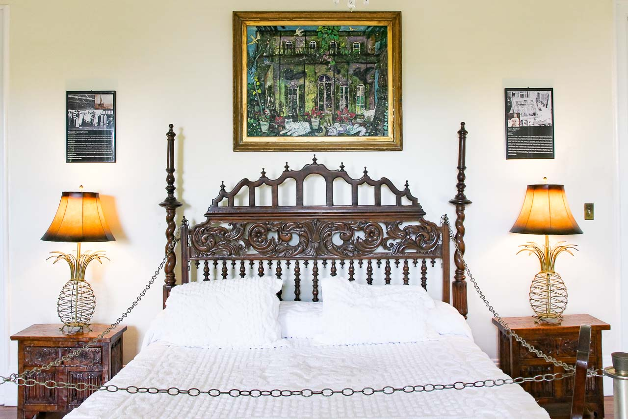 Main bedroom of Hemingway's Home, Key West with ornate wooden bedhead and pineapple lamps