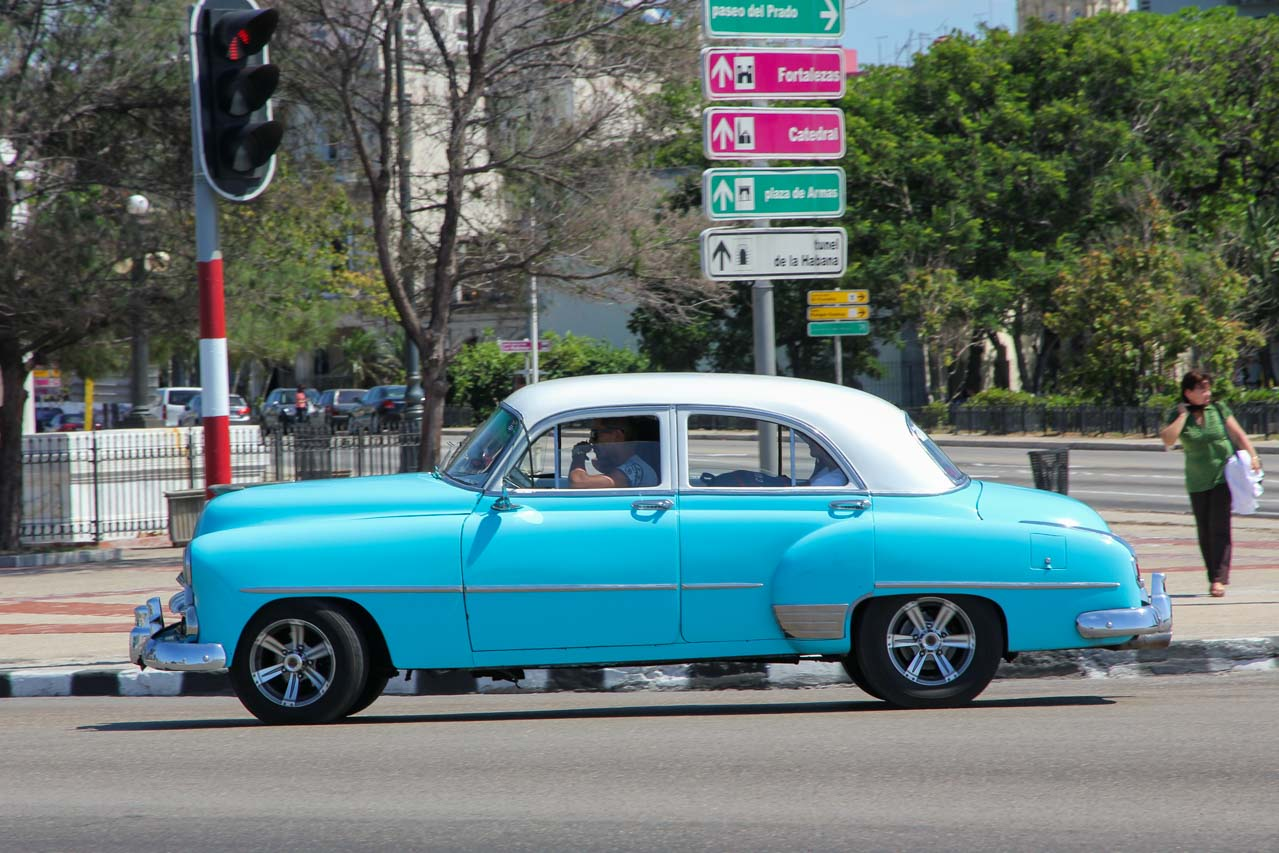 Aqua and white classic car driving through intersection