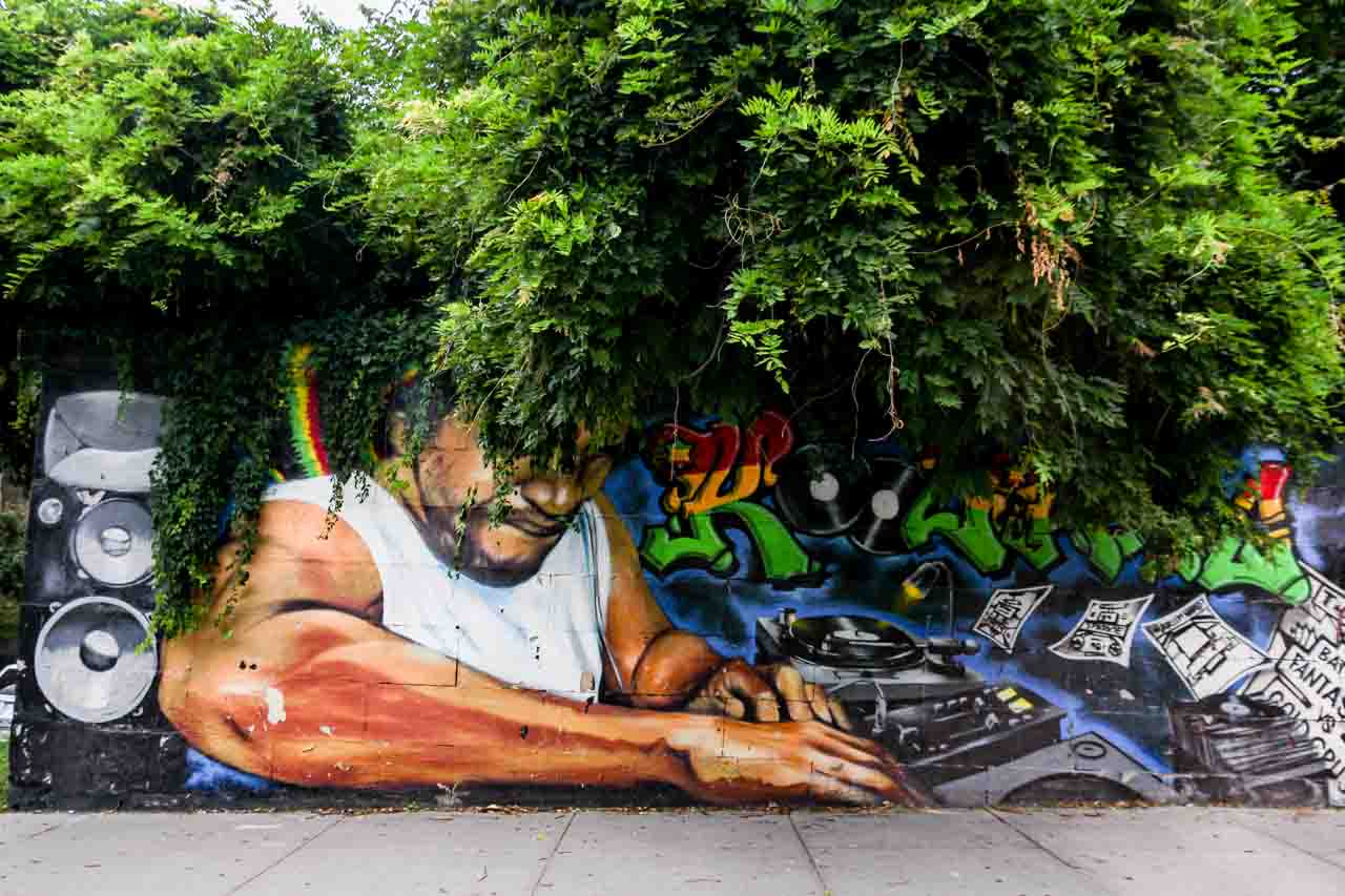 Mural tribute to DJ Kool Herc with bush growing over the wall