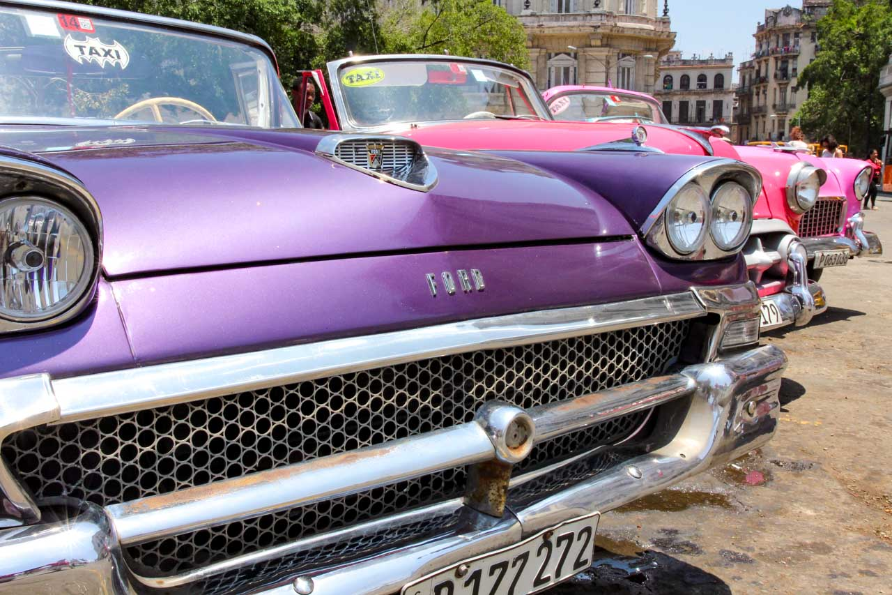 A line up of classic cars beginning with a purple Ford