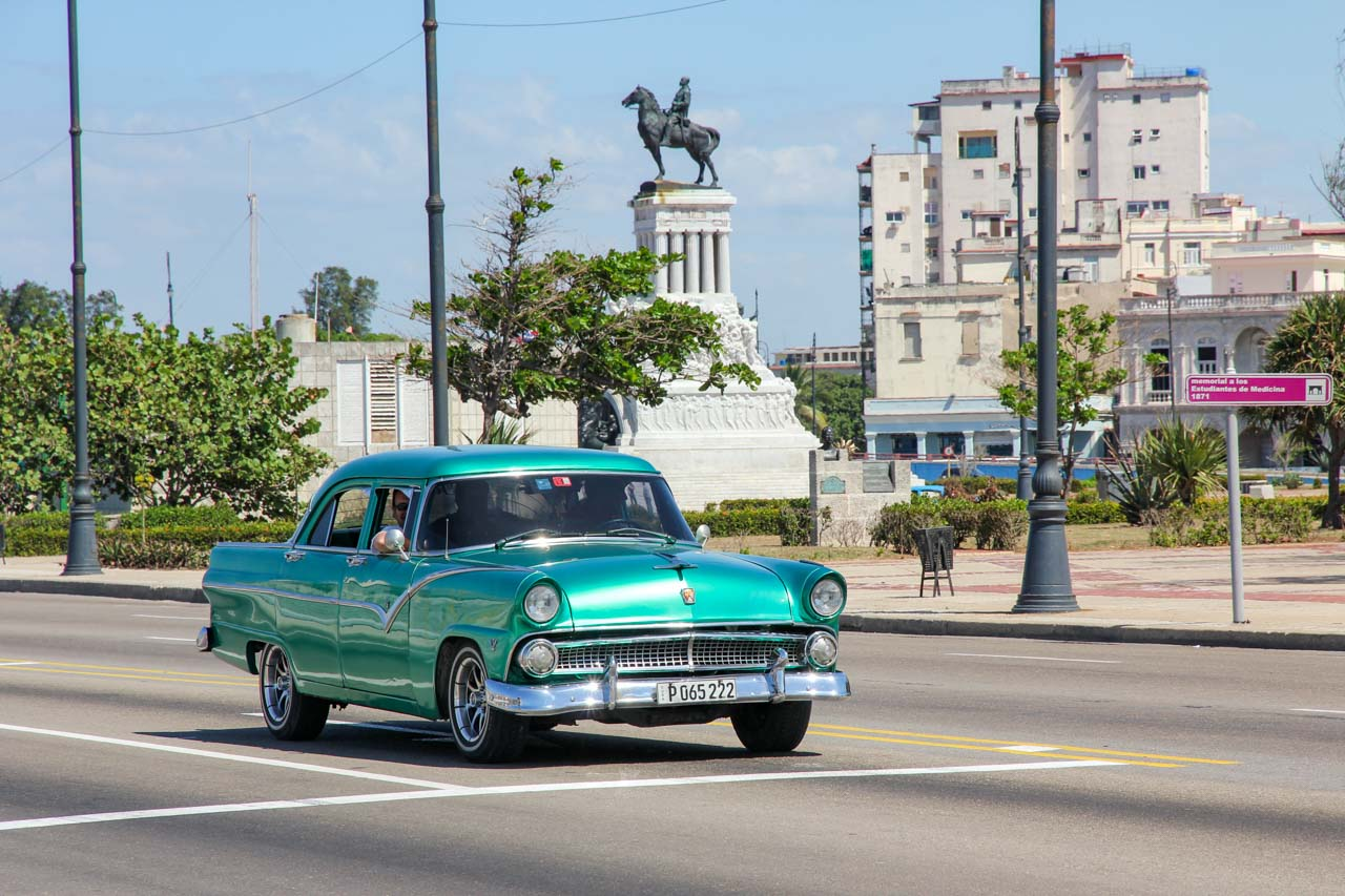 Aqua, vintage Ford Fairlane stopped at an intersection, with monument in background