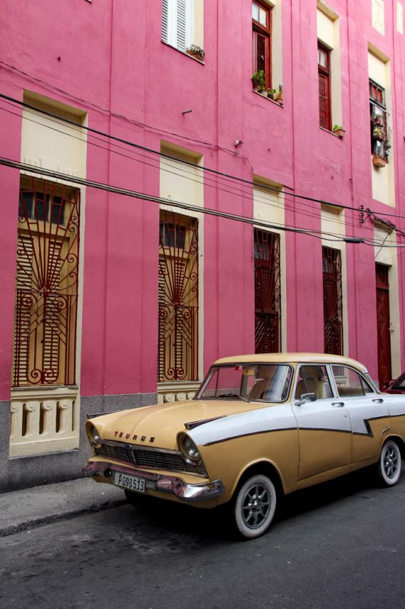 Taurus in beige and white parked infront of a pink building