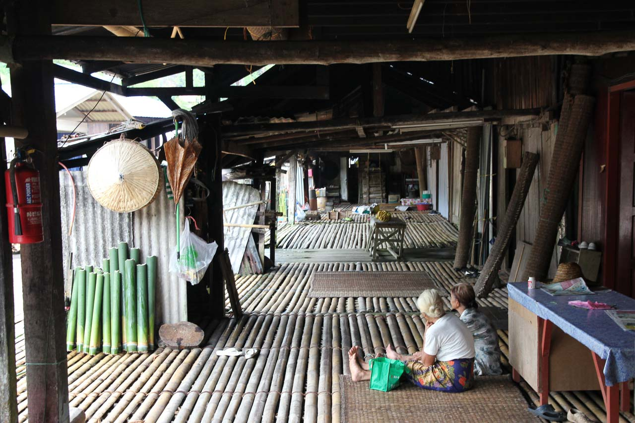 Women seated on floor of bamboo longhouse