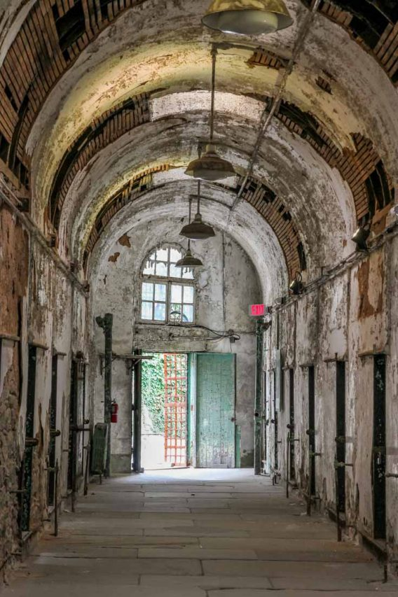 Arched corridor with open door at the end