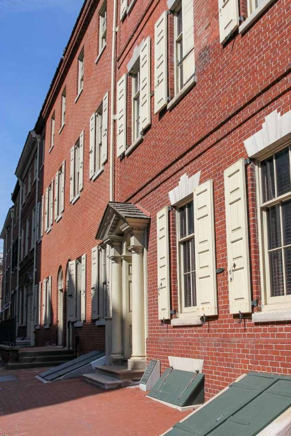 Photo of historic, red brick town homes with cream shutters