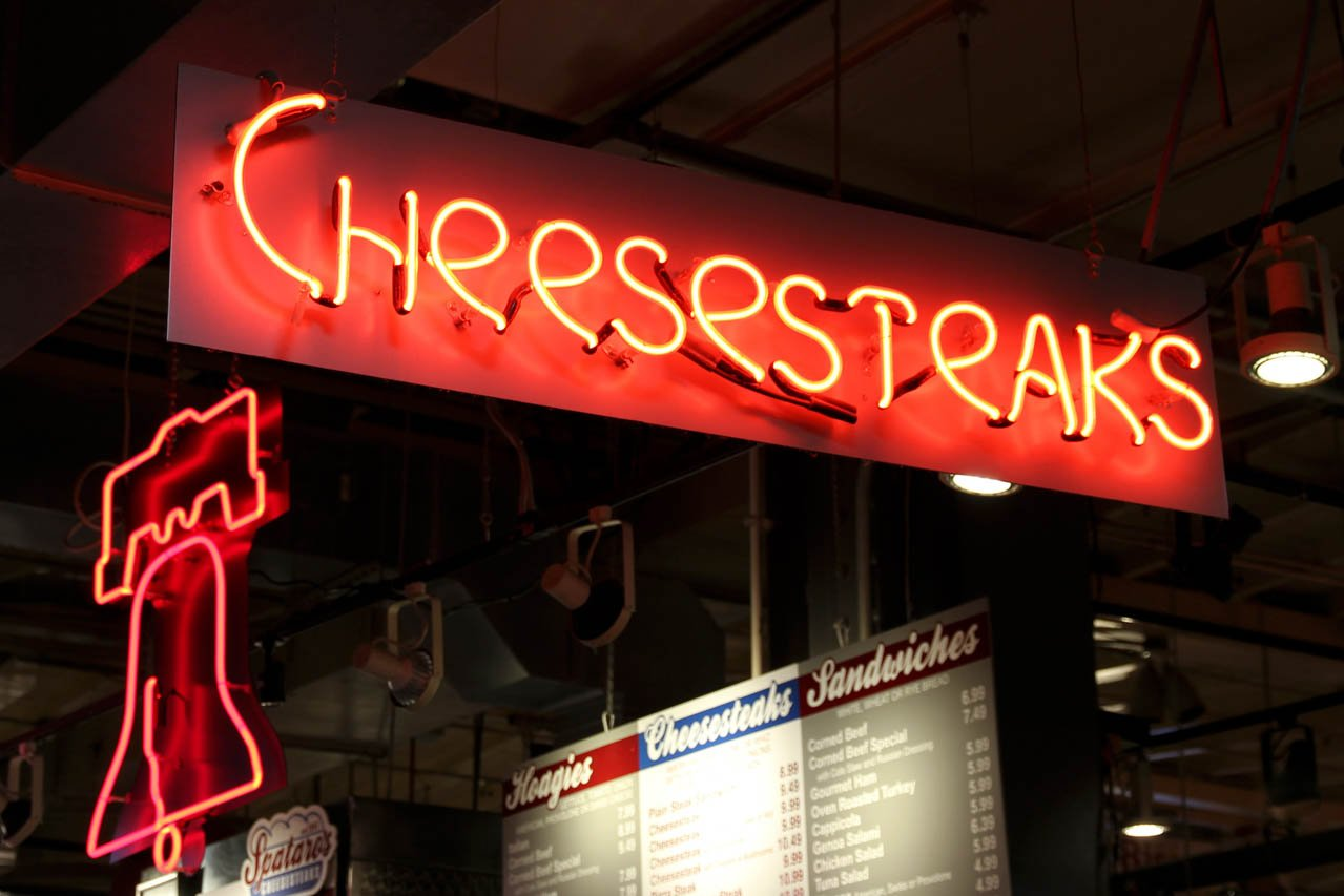 """Neon sign reading """"cheesesteaks"""" and another in the shape of the Liberty Bell"""