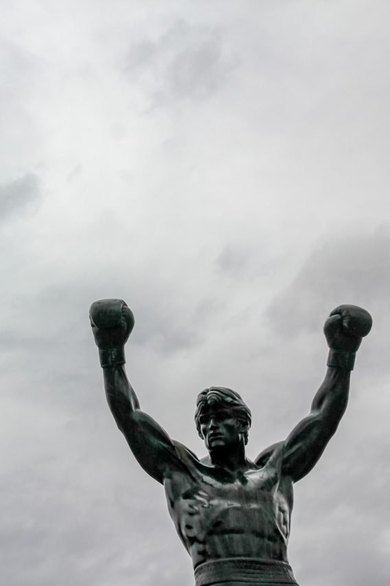 Top half of Rocky Statue with raised arms and boxing gloves against cloudy sky