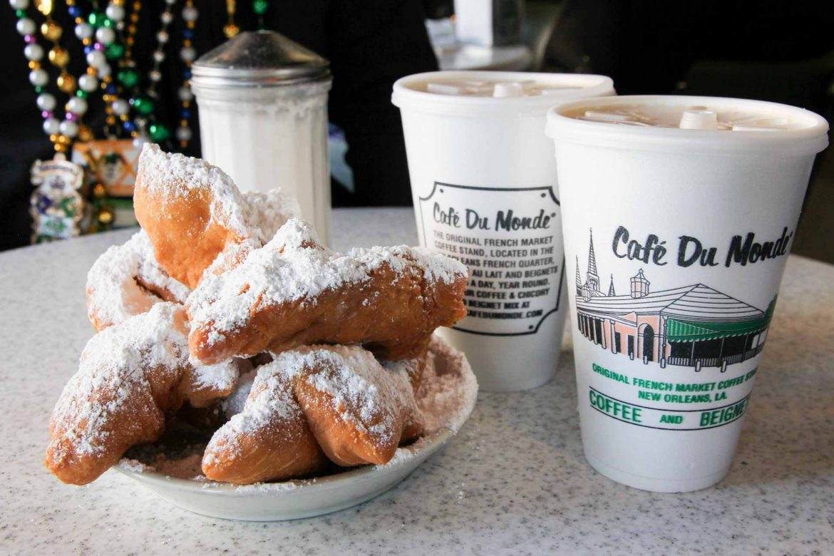 White plate piled high with beignets and two disposable coffee cups reading Cafe Du Monde