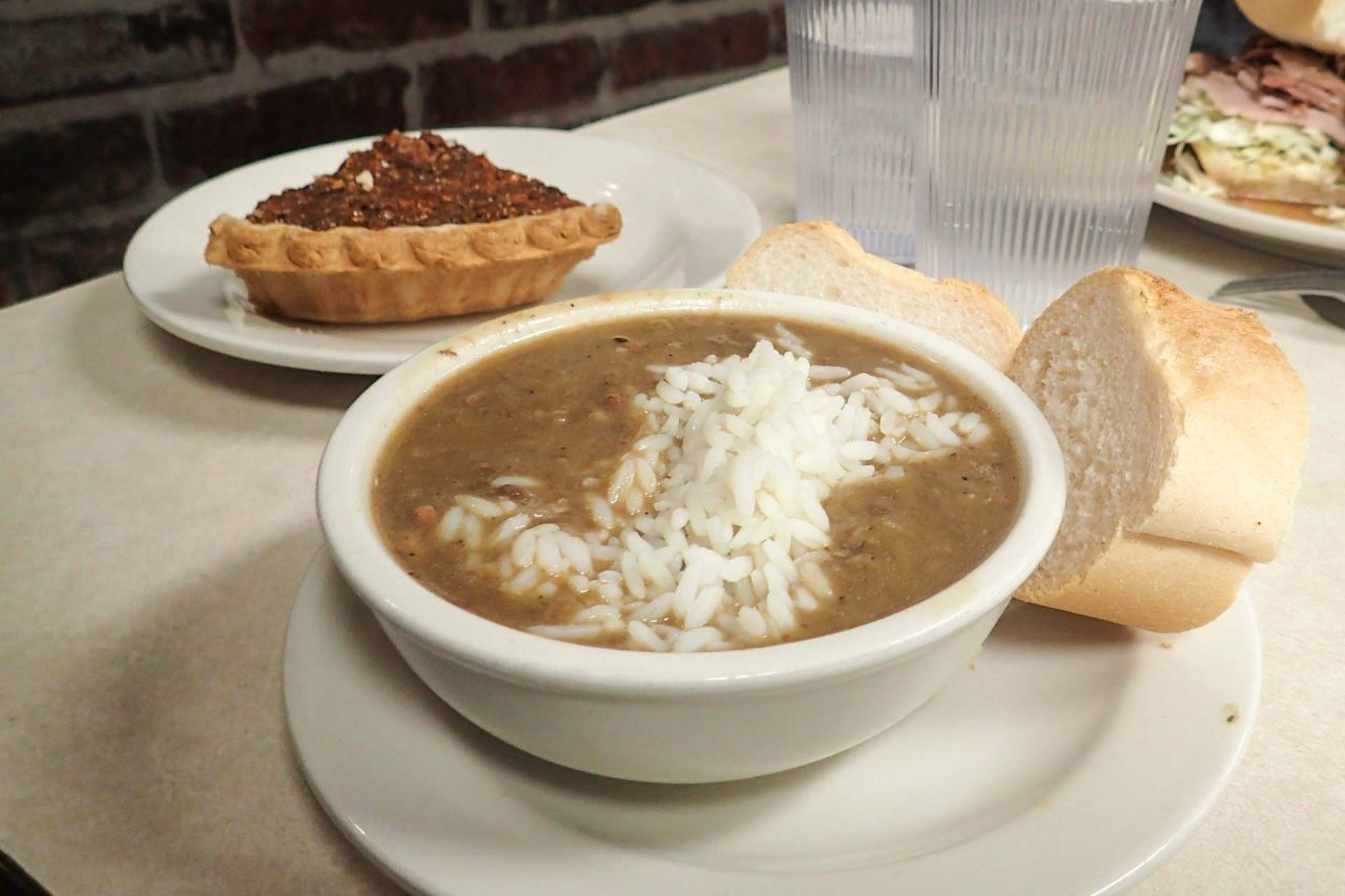 Bowl of Gumbo with bread on the side and slice of pecan pie in the background