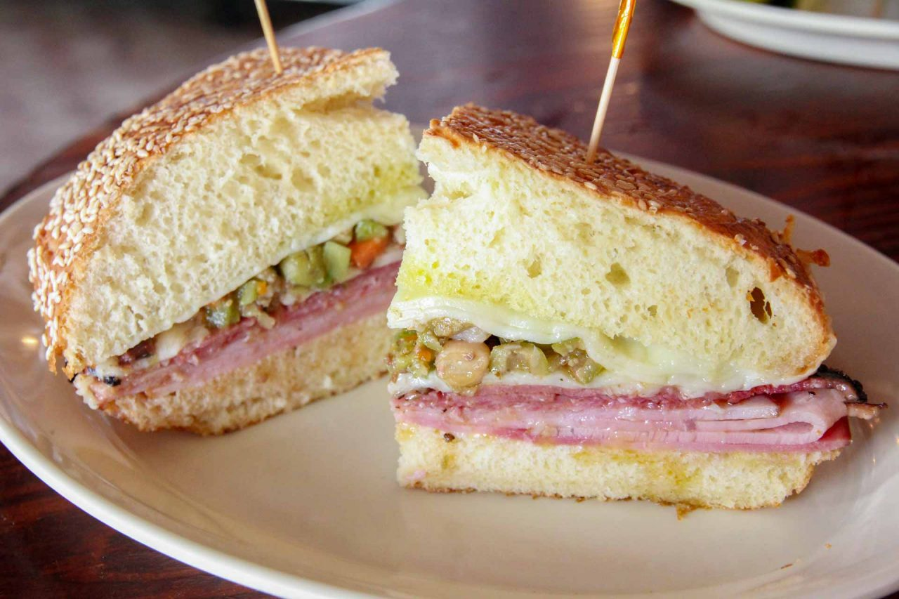 Close up of Muffaletta sandwich served on white plate - Must-Eat New Orleans Foods