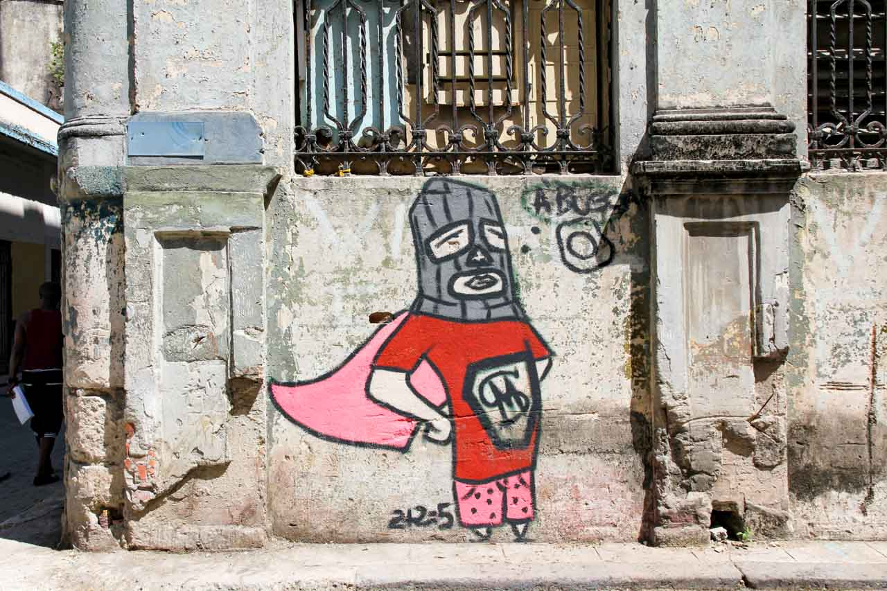 Street art of person in super hero costume and ski mask