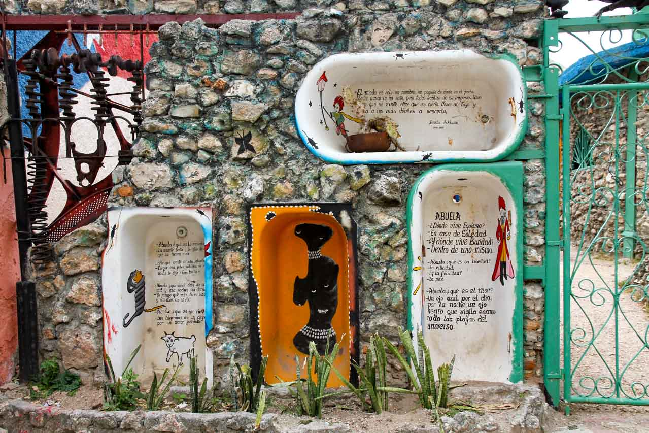 Poetry and art painted on bathtubs set into a stone wall