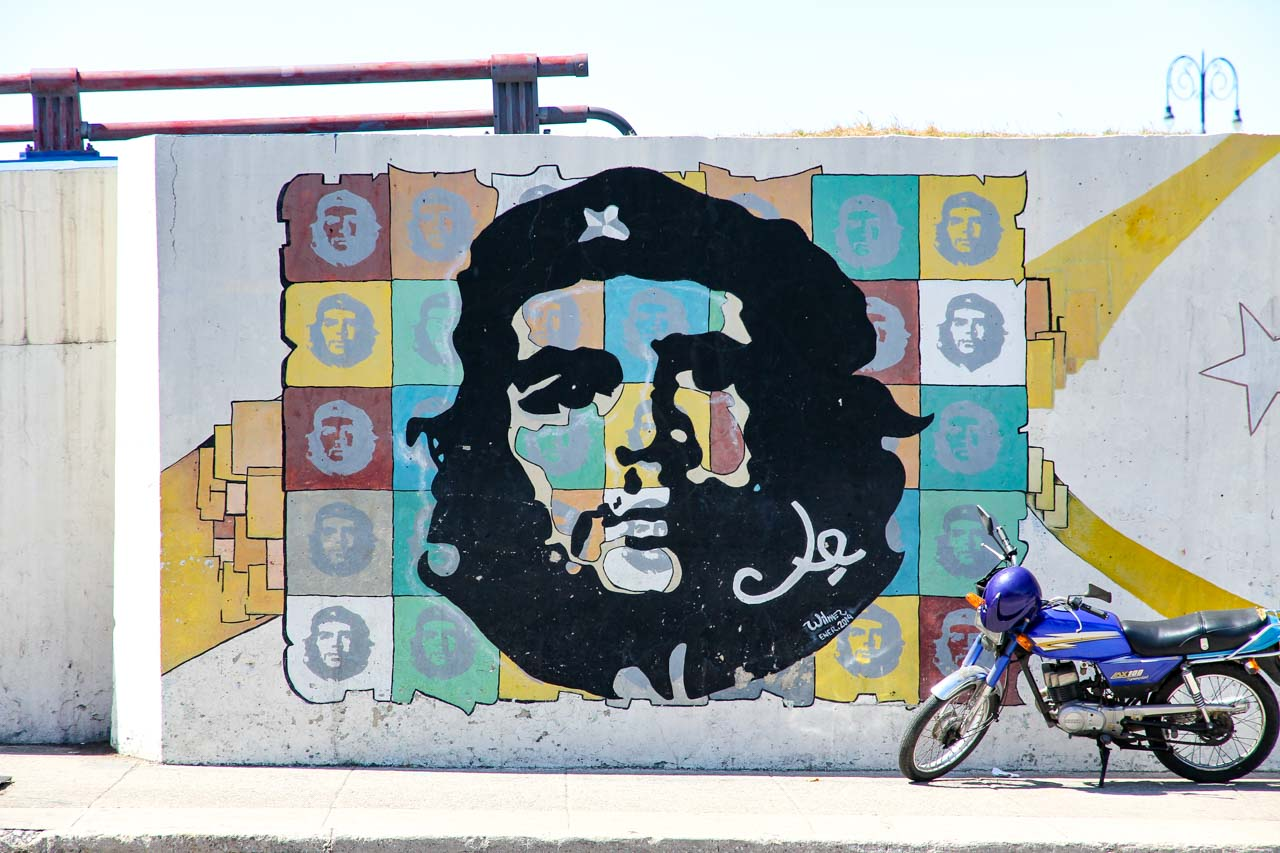 Pop art style Che Guevara portrait on a white wall, with blue motorbike parked infront