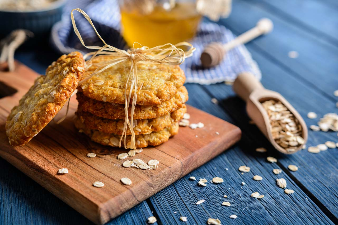 ANZAC biscuits tied with brown string on a wooden board with a spoonful of oats and honey in background