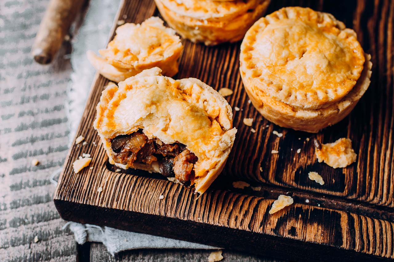 Single serve meat pies on a wooden cutting board