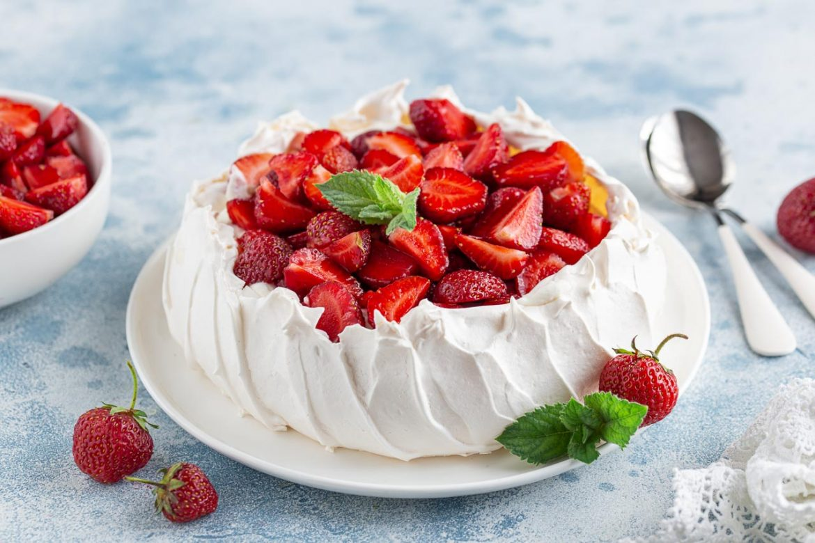 Pavlova with strawberries on white plate and blue tabletop