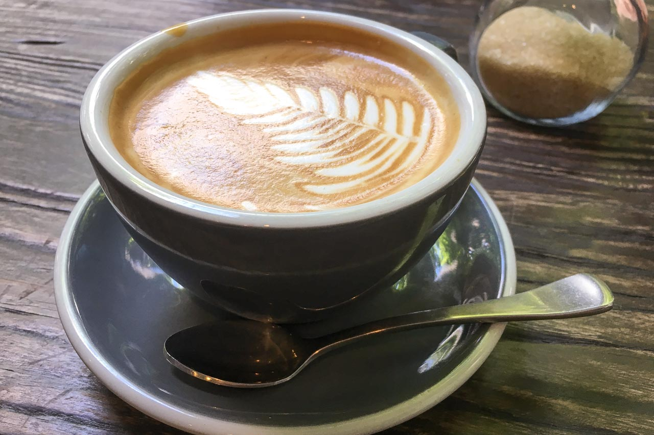 Latte on wooden tabletop with sugar bowl in background