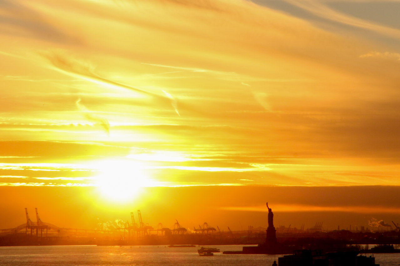 Sunset view of the Statue of Liberty and silhouette of industrial port