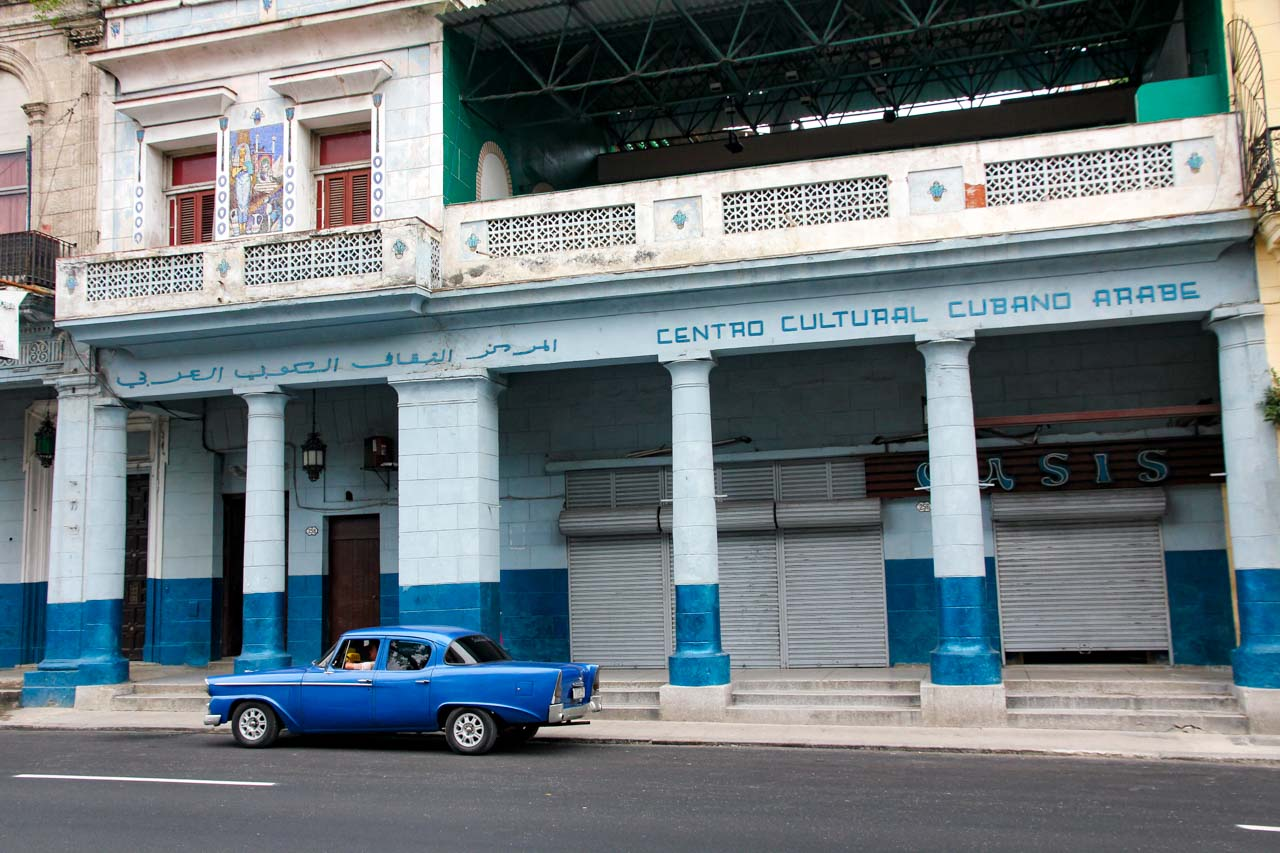 Blue classic car parked infront of blue building