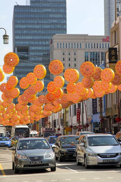 Coin-shaped lanterns hanging over traffic in Chinatown street