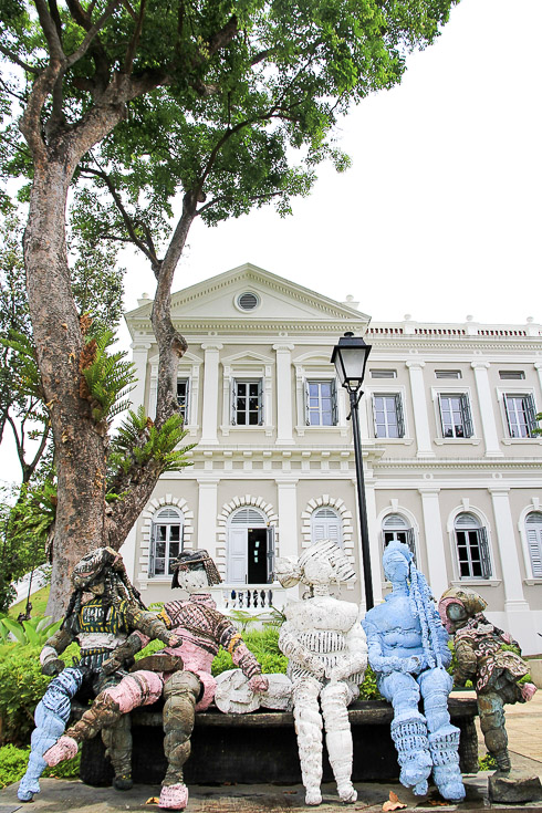 Photo of National Museum of Singapore with sculpture of peple on park bench in foreground