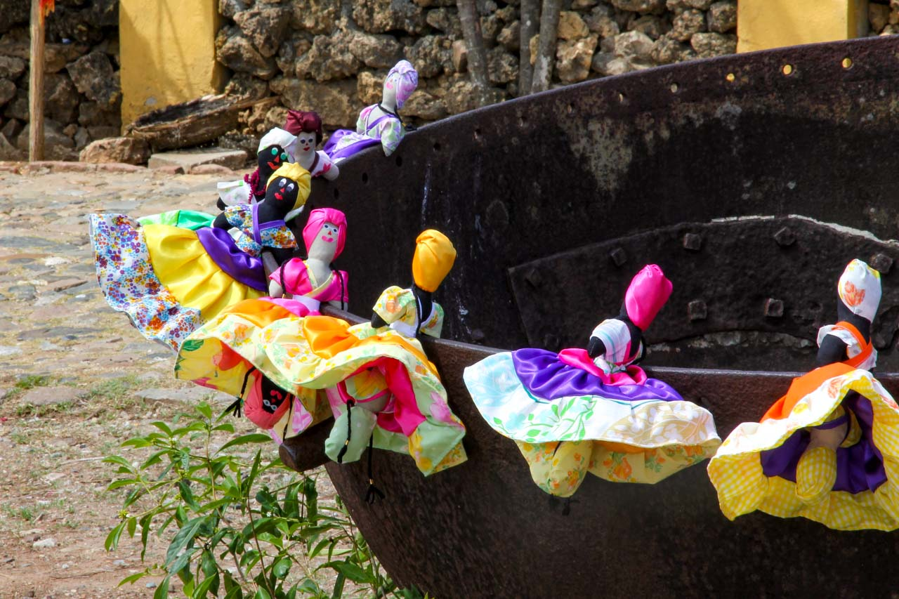Reversible dolls for sale, hung on the side of an old sugar kettle