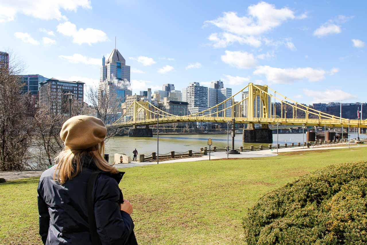 Woman looking at a yellow bridge with city skyscrapers in background