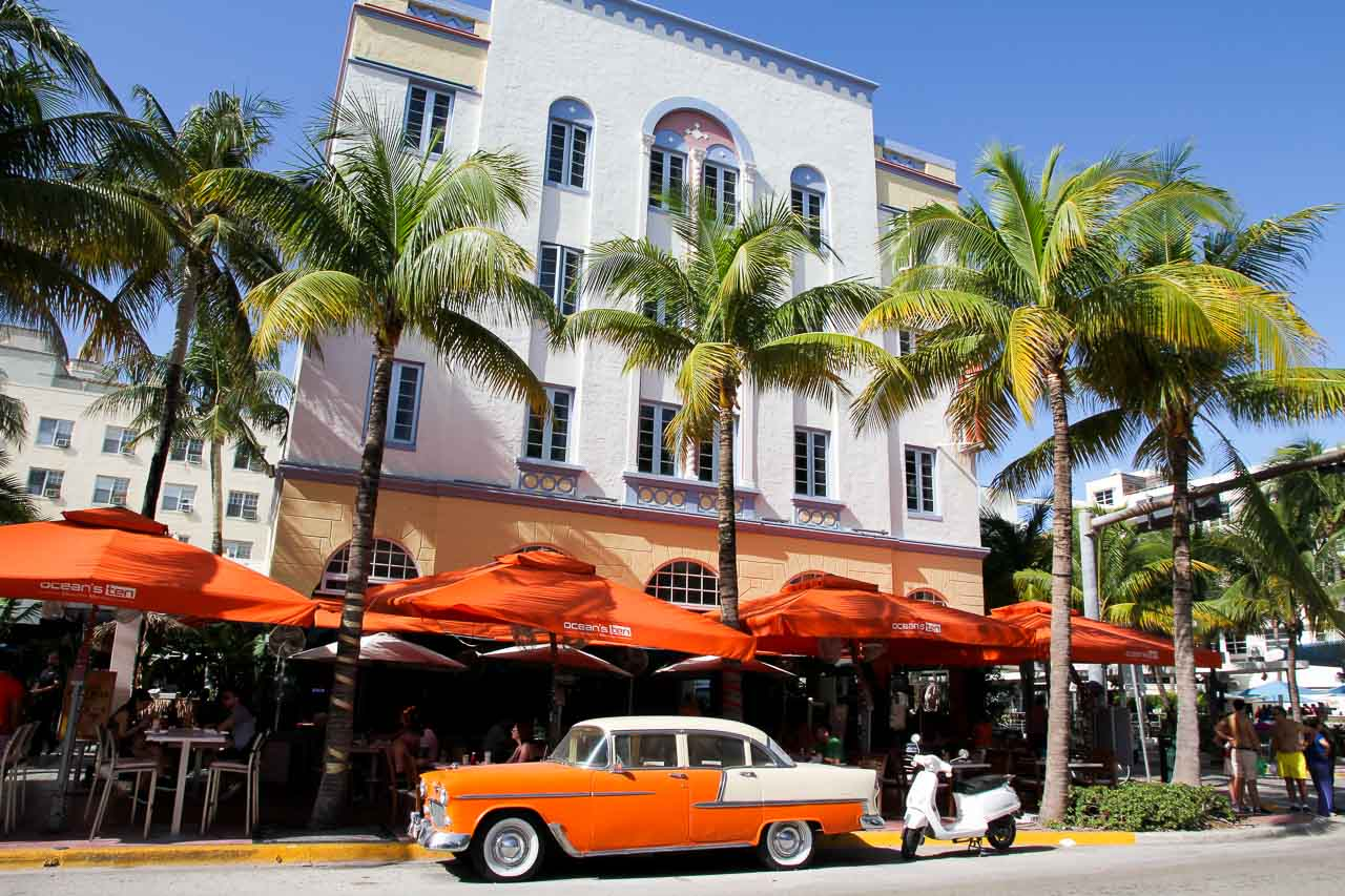 Orange and white vintage car parked infront of hotel with palm trees and orange umbrellas