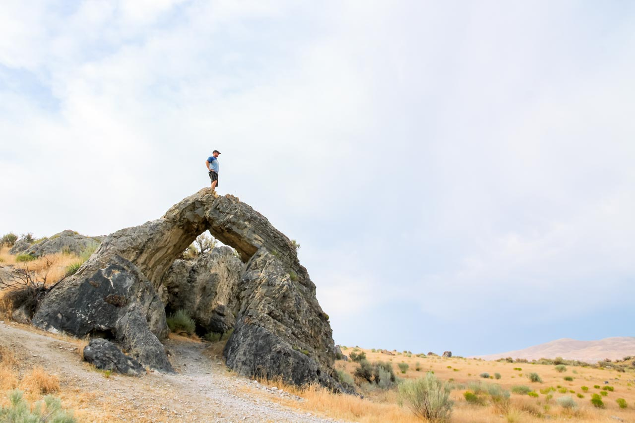 Man standing on top of rock arch looking out at landscape