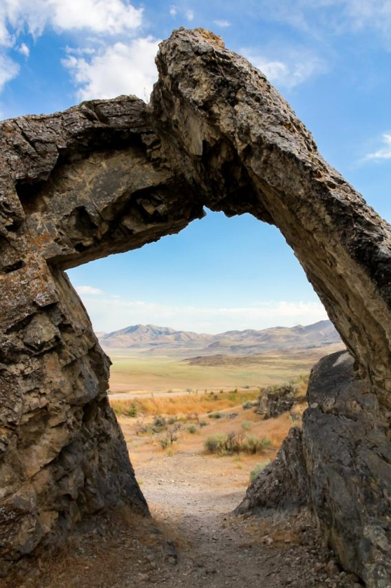 Photo of desert and arid mountains through a rock arch