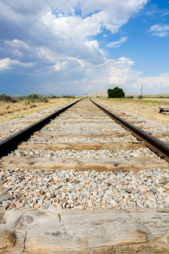 Railroad leading off into the distance with partly cloudy sky and desert landscape