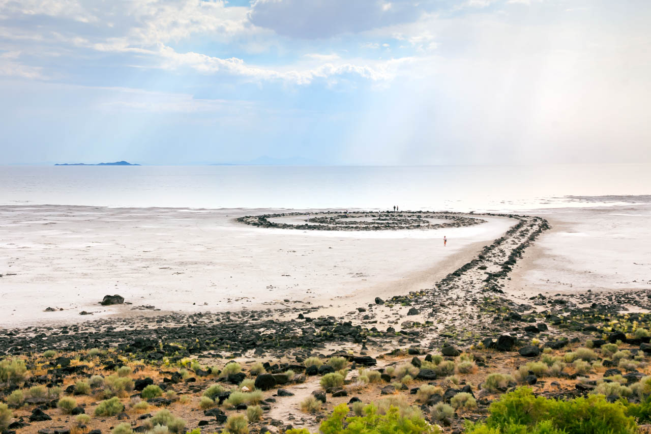Photo of Spiral Jetty made of stones with sun rays falling on Great Salt Lake in background