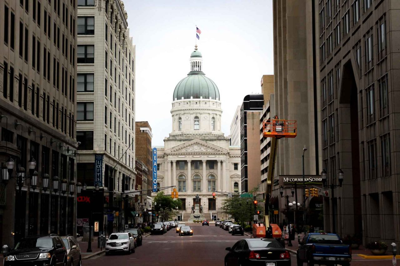 Indiana State Capitol viewed down city street, framed by buildings