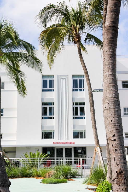 Facade of white art deco building with palm trees in foreground