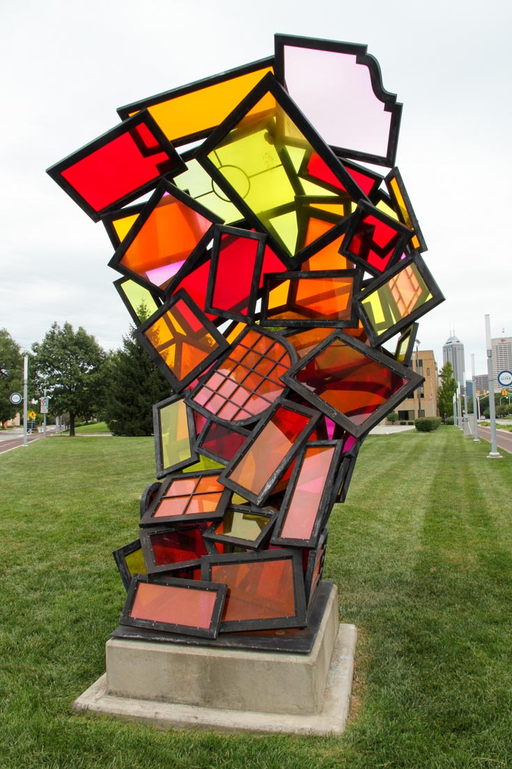 Outdoor sculpture made of coloured glass panels in red, orange, pink and yellow.