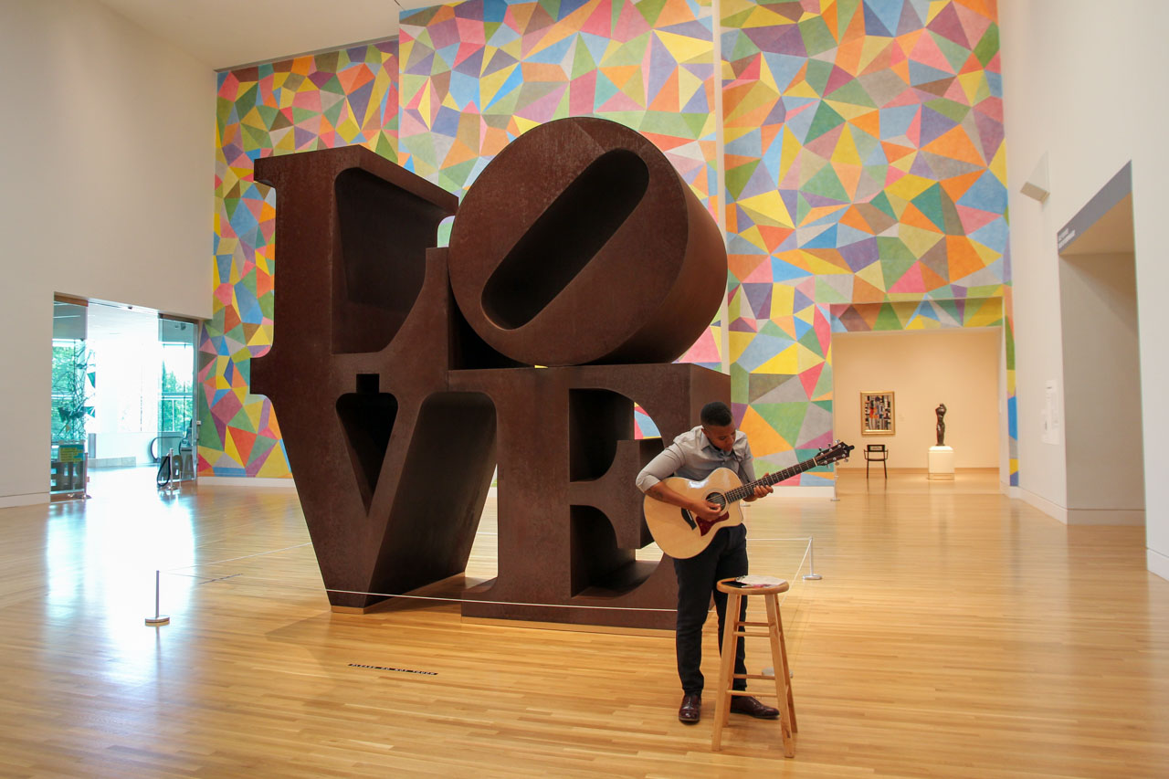 """Rusted sculpture of word """"Love"""" with colourful wall behind and man with guitar in foreground"""