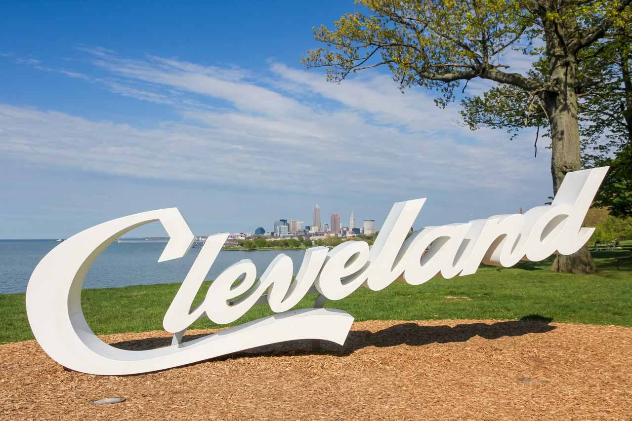 """Sign reading """"Cleveland"""" in parkland with Lake Erie and city skyline in the background"""