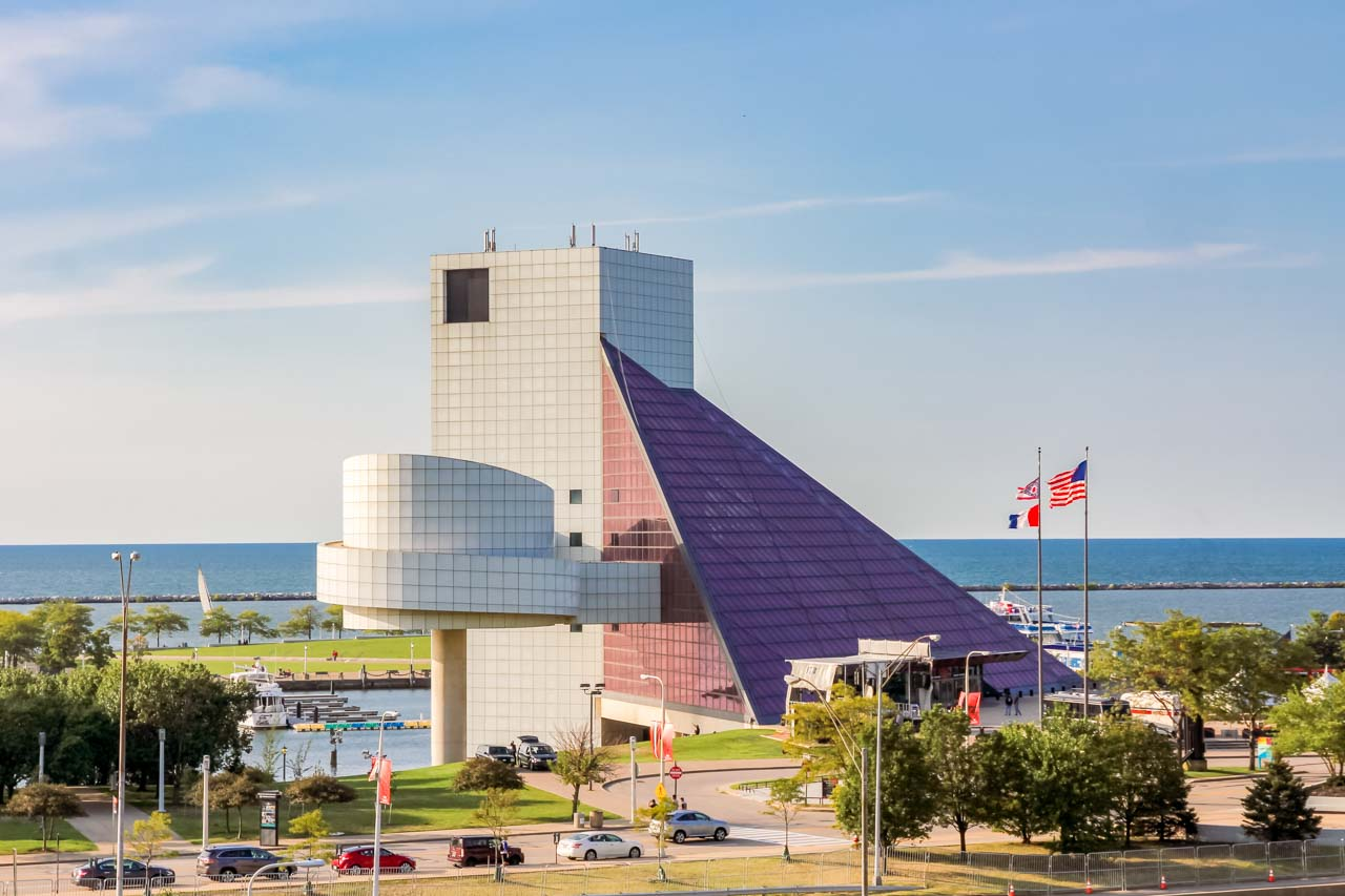 Photo of the exterior of Rock & Roll Hall of Fame with Lake Erie in the background.