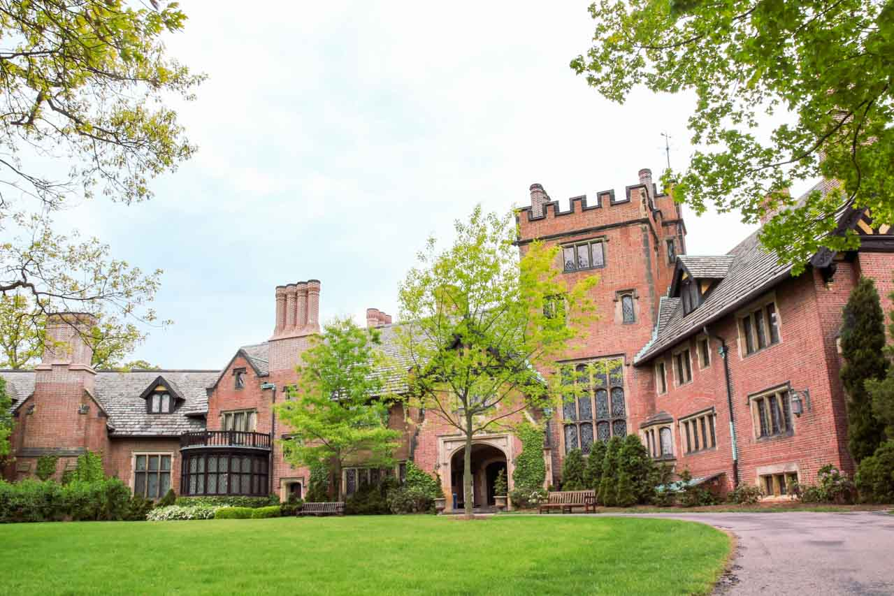 Photo of front exterior of a Tudor Revival mansion framed by trees and lawn.