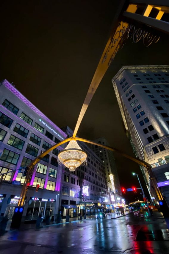Photo of giant outdoor chandelier over street lined in theaters