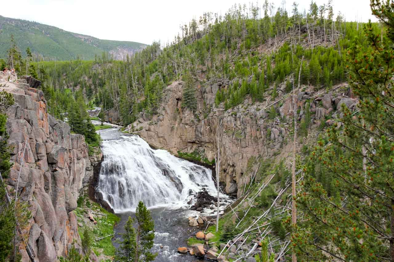 Photo of water fall cascading into rock walled canyon from above